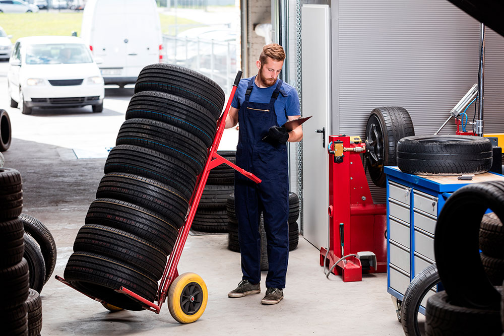 Man With Stack of Tires On Dolly